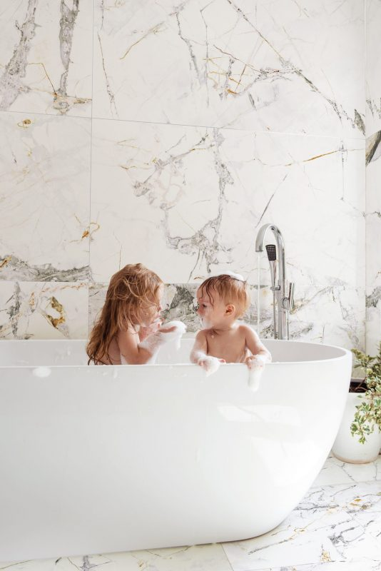 Brother and sister bathe in a foam bath